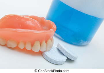 Denture with cleaning tablets and water glass