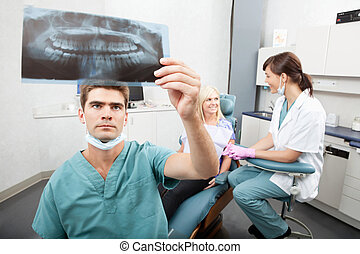 Dental Clinic - Radiodentist checking x-ray with assistant...