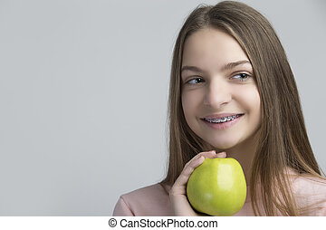 Dental Concepts. Portrait of Happy Teenage Female With Teeth Brackets. Posing With Green Apple and Smiling Against White