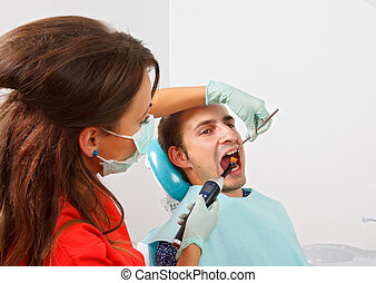 Dental filling - The dentist is filling the patient's tooth