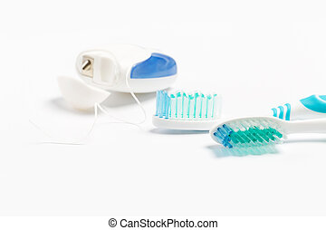 Dental floss and toothbrush isolated on a white background.
