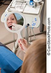 Dental floss instructions - Female patient receiving dental...