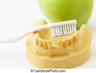 Dental health care concept, green apple and toothbrush