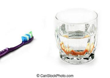 Dental health concept: partial denture inside glass next to...
