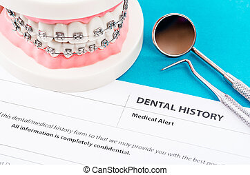 Dental history form with model tooth and dental instruments.
