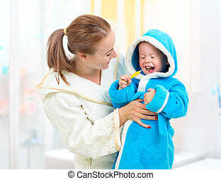 Dental hygiene in bathroom. Mother and child cleaning teeth together.