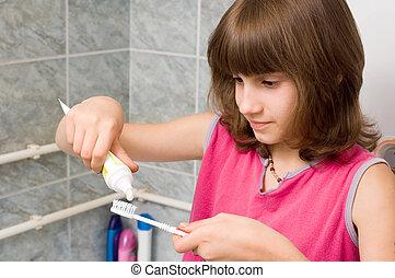 Dental hygiene - Young child brushing her teeth in bathroom
