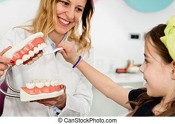 Dental Hygiene - Dentist with little girl, explaining...