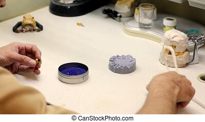 Dental implants laboratory. Dental technician working with wax seals, as a framework for metal ceramics.
