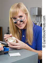 Dental lab technician with surgical loupes applying porcelain to dentition mold in a lab