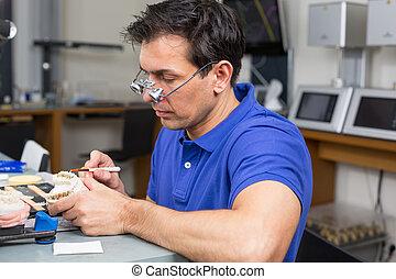 Dental lab technician appying porcelain to mold - Dental lab...