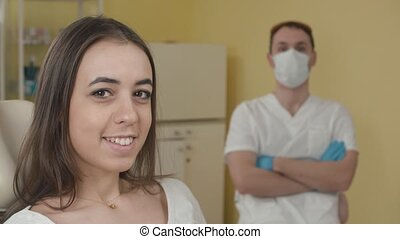 Dental office. Happy female patient looking at the camera. in the background a dentist. The concept of advertising