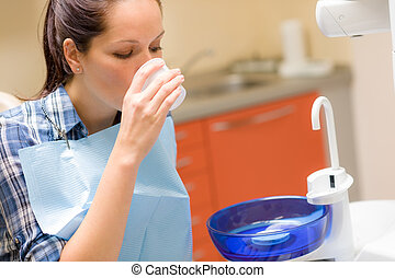 Dental patient woman wash mouth after treatment