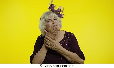 Dental problems. Frustrated senior old woman touching sore cheek, upset with terrible toothache, horrible pain from cavities and gum disease. Elderly stylish grandma on yellow background. 6k footage