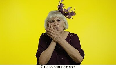 Dental problems. Unhealthy senior old woman touching sore cheek, suffering terrible toothache, horrible pain from cavities and gum disease. Elderly stylish grandma on yellow background. 6k footage