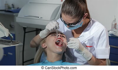 Dental surgeon applies dental probe to examine patient's...
