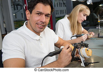 Dental technician working on a dental prosthesis in an articulator