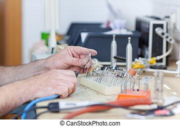 Dental Technician With Drill In Laboratory