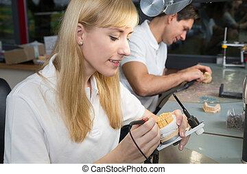Dental technician working at articulator
