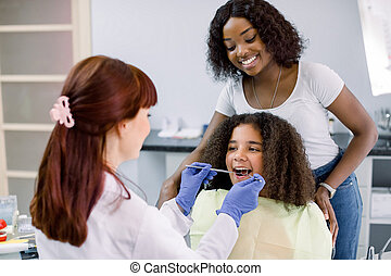 Dental treatment without fear. Female dentist in whilte uniform and gloves, examining teeth of little African American girl, while her mother supporting her behind, at modern pediatric dental clinic