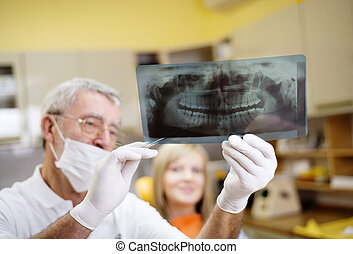 Dental visit - Dentist is showing the x ray of teeth to his...