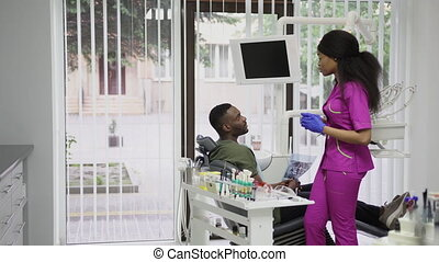 Dentisry concept, healthcare, oral care. Young beautiful african woman dentist discusses the strategy of treatment with the patient, african man, sitting in the chair and holding xray image of jaws