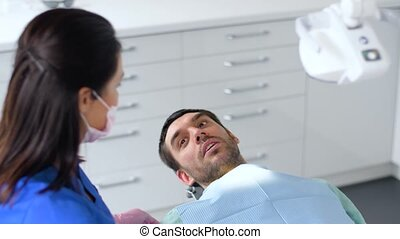 dentist adjusting patient chair at dental clinic - medicine,...