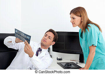 Dentist Analyzing X-Ray With Assistant