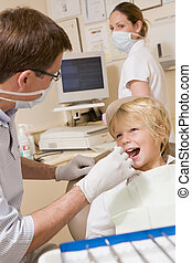 Dentist and assistant in exam room with young boy in chair