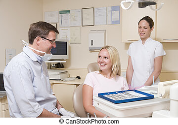 Dentist and assistant in exam room with woman in chair smiling