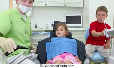 Dentist and boy take dental tools and put it in mouth of girl