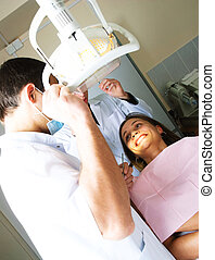 dentist and his assistant examine a patient
