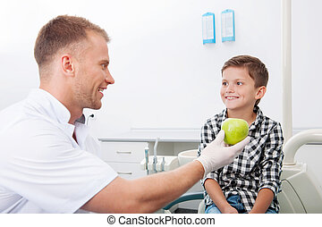 Dentist and little patient. Cheerful young dentist giving an apple to little boy