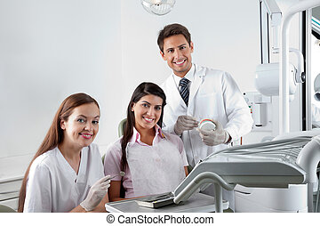 Dentist And Nurse With Patient In Clinic - Portrait of happy...