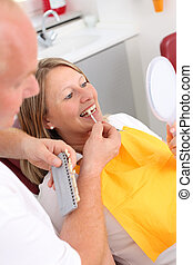 Dentist And Patient Comparing Teeth While Looking In Mirror...