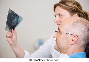 Dentist And Patient Examining Xray In Clinic