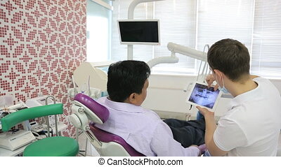 Dentist and patient man, discuss treatment with your tablet...
