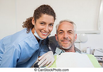 Dentist and patient smiling at camera