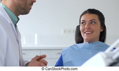 dentist and patient talking at dental clinic - medicine,...