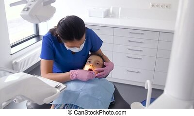 dentist checking for kid teeth at dental clinic - medicine,...