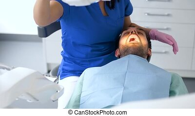dentist checking patient teeth at dental clinic - medicine,...