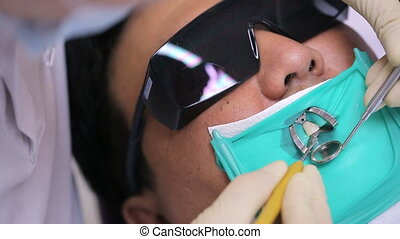 Dentist checks status of installed curing fillings in oral cavity with a rubber dam.