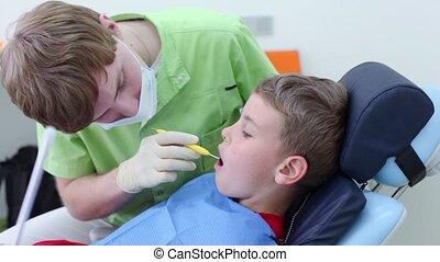 Dentist checks teeth of boy by dental mirror in surgery