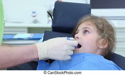 Dentist checks teeth of girl by dental mirror in surgery