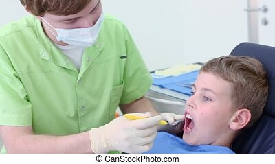 Dentist checks teeth of little boy with dental mirror in surgery