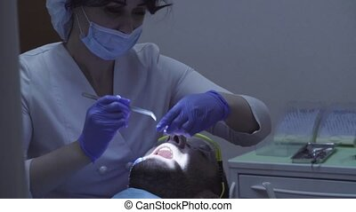 Dentist curing tooth in dental clinic - Woman dentist curing...