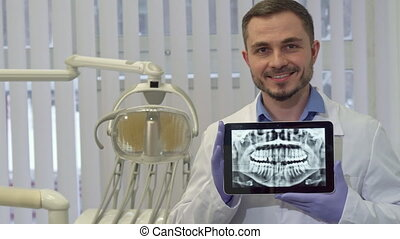 Dentist demonstrates the x-ray of human teeth on his tablet