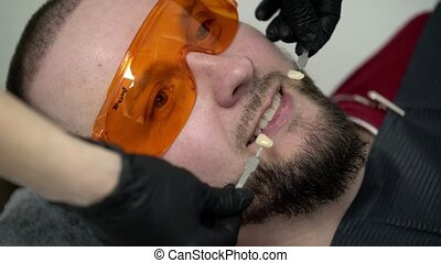 Dentist doctor checking whiteness of the teeth