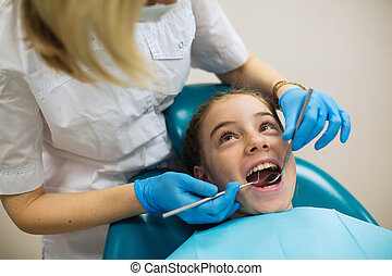 Dentist doing teeth checkup of teen girl in a dental chair at medical clinic.