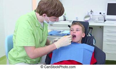 Dentist examines teeth of boy by dental mirror in surgery